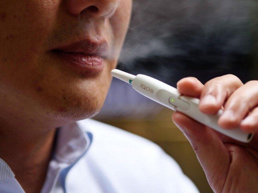 Мужчина курит IQOS